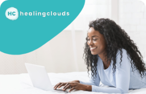 A woman smiling while typing on her laptop, with the words healingclouds in a blue bubble above her