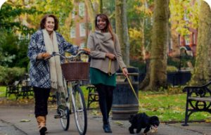 Two women walking together, the one on the left is pushing her bike, while the woman on the right is walking her dog