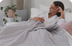 Woman smiling in her bed, under a grey weighted blanket
