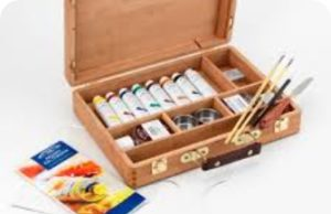 A wooden box containing a multitude of paints and paint brushes
