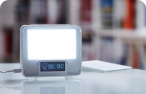 A lamp screen on a table, with a battery percentage of 90 below it