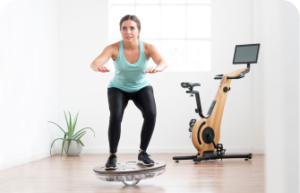 A woman balancing on a balance board in front of an exercise bike