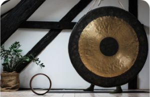 A black and gold gong hanging in front of some wooden beams and a plant