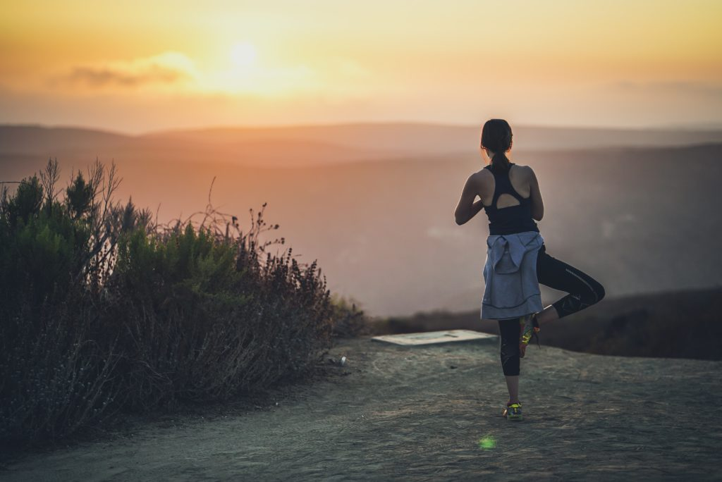Person practicing yoga at sunrise