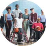 Group of people in sports attire, two wheelchair basketball players are in the foreground